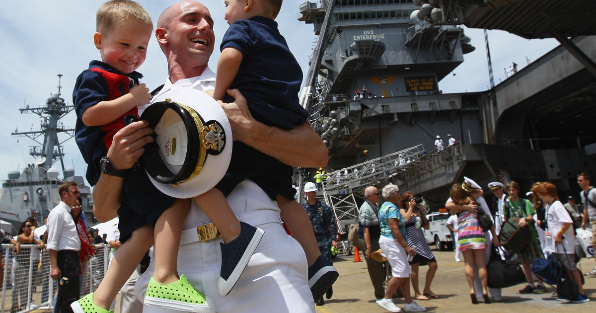Lt. Brian Dennison of the USS Enterprise hugs his twin boys Logan and Grant at Norfolk Naval Station in Virginia July 15, 2011, after 184 days away, supporting operations in Afghanistan and Iraq.</p>
