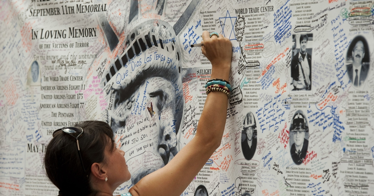 A woman writes a message on the wall of remembrance memorial near the World Trade Center on Sept. 10, 2011 in New York. U.S. President Barack Obama on Saturday called for a