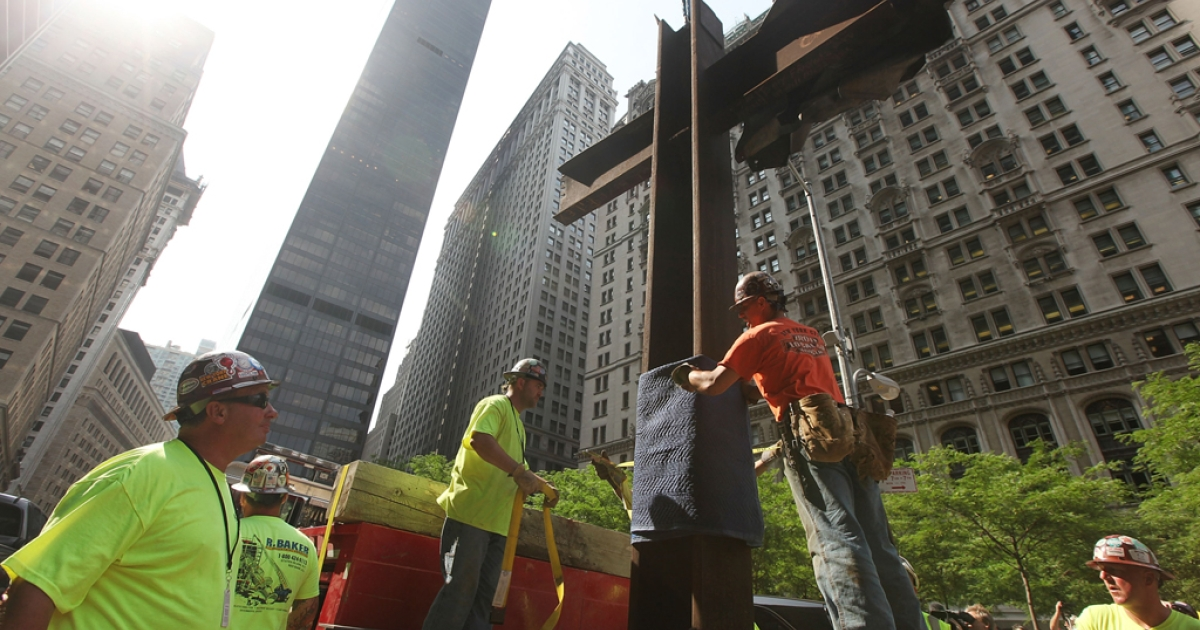 Workers prepare the World Trade Center cross to be moved into its permanent home at the 9/11 Memorial Museum after a blessing ceremony on July 23, 2011 in New York City. The cross is an intersecting steel beam discovered in the World Trade Center rubble which served as symbol of spiritual recovery in the aftermath of 9/11.</p>