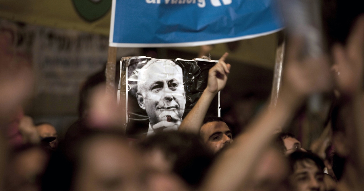 Israeli demonstrators taking part to a protest against rising housing prices and social inequalities in the Jewish state, hold up a wrinkled poster of Prime Minister Benjamin Netanyahu in the centre of the coastal city of Tel Aviv on August 6, 2011.</p>