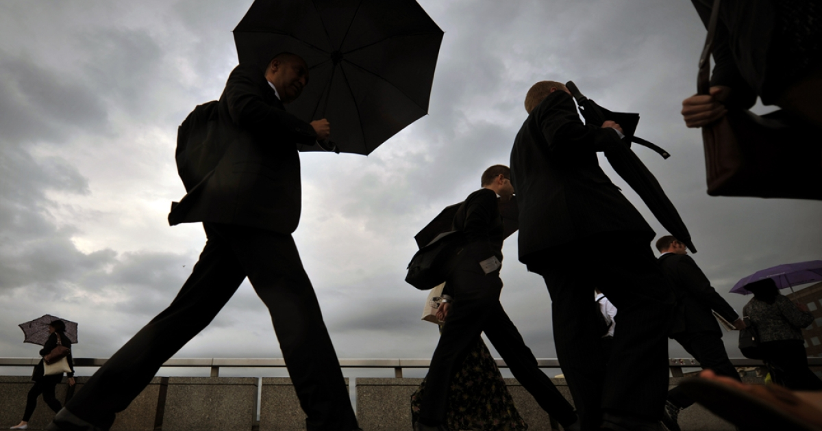 City workers walk over London Bridge in central London, on August 18, 2011.</p>