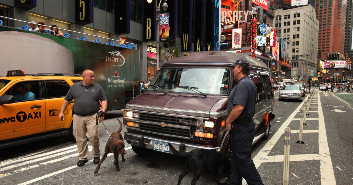 New York Police Department Bomb Squad detectives and K9 dogs investigate a vehicle after it was parked near Times Square with its headlights on, September 10, 2011 in New York City.</p>