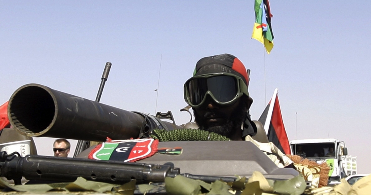 A Libyan National Transition Council (NTC) fighter arrives in an armored vehicle on the frontline of Bani Walid, southeast of Tripoli, on Sept. 17, 2011.</p>