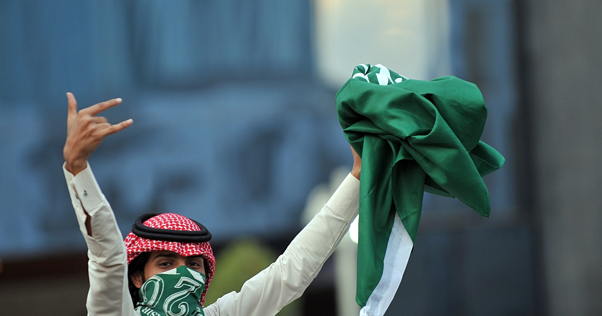 A Saudi youth holds up a folded national flag during celebrations of the 81st Saudi Arabian National Day in the desert kingdom's capital Riyadh on September 23, 2011.</p>