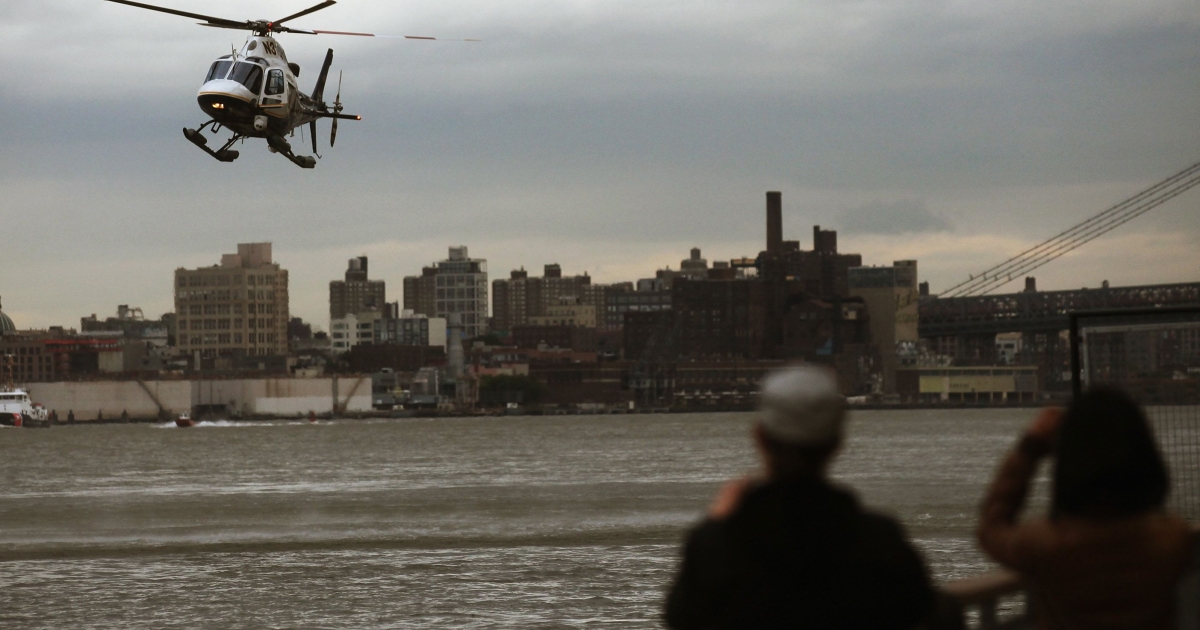A New York Police Department helicopter hovers over the East River before landing after a helicopter crash on October 4, 2011 in New York City during a birthday joyride.</p>