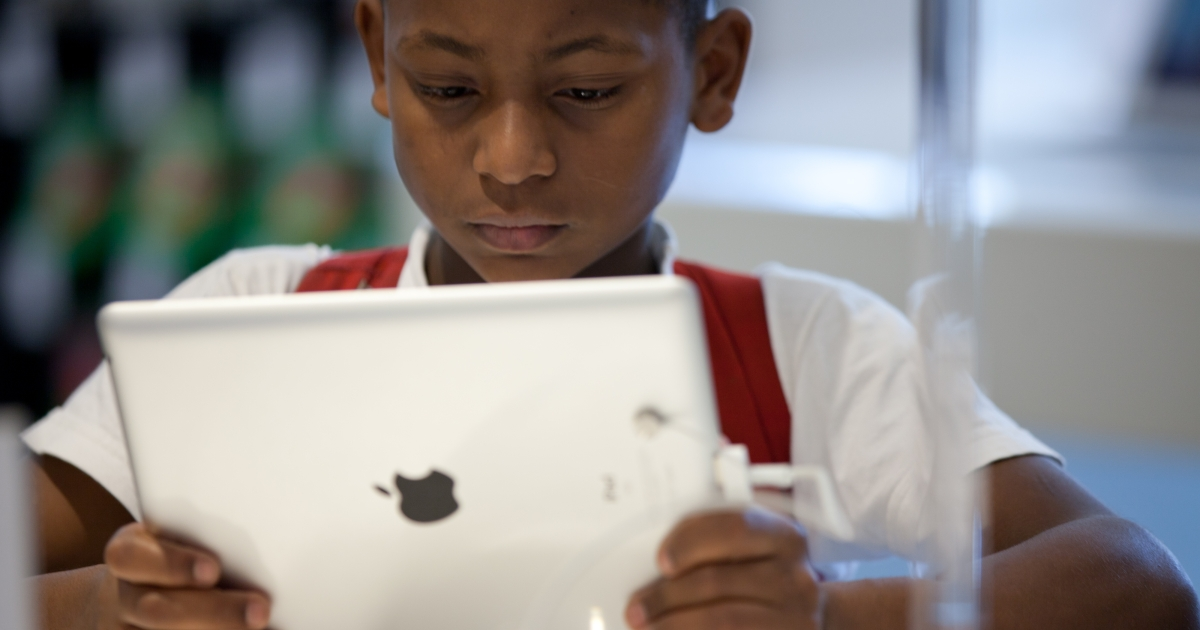A Brazilian boy looks at an iPad at the retail shop of Apple products in Sao Paulo.</p>