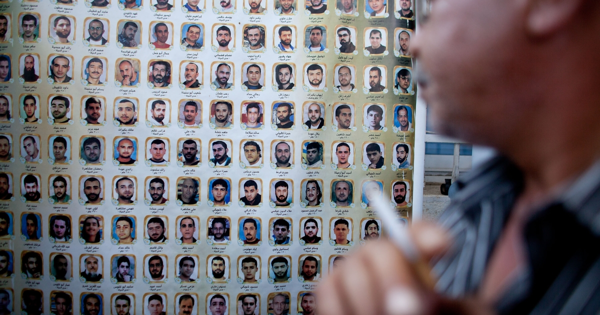 A Palestinian man looks at a banner bearing names and photos of Palestinian prisoners held in Israeli jails during a protest calling for the release of Palestinian prisoners, outside the International Red Cross building on October 14, 2011 in east Jerusalem, Israel</p>