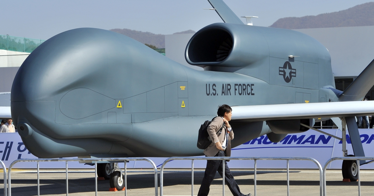 A man walks past a US Air Force Global Hawk unmanned aerial vehicle hanger during a preview day of the Seoul International Aerospace and Defense Exhibition at a military air base in Seongnam, south of Seoul, on October 17, 2011.</p>