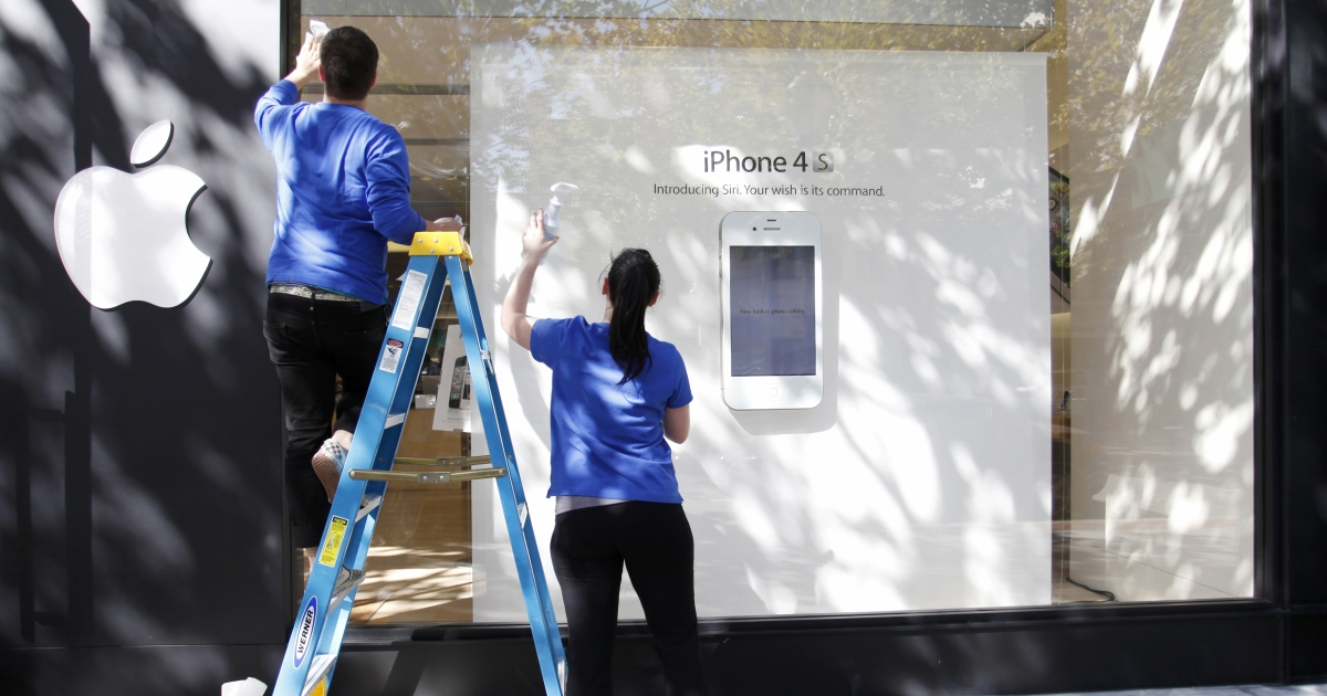 Apple employees from the Palo Alto Apple Store clean the store window .</p>