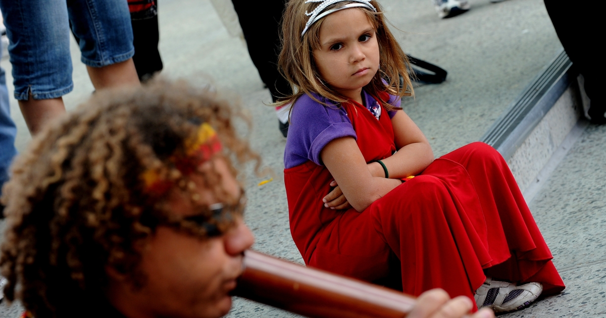 A young girl (R) watches as a protester plays a didgeridoo as the Commonwealth Heads of Government Meeting (CHOGM) starts in Perth on 28 October 2011.</p>