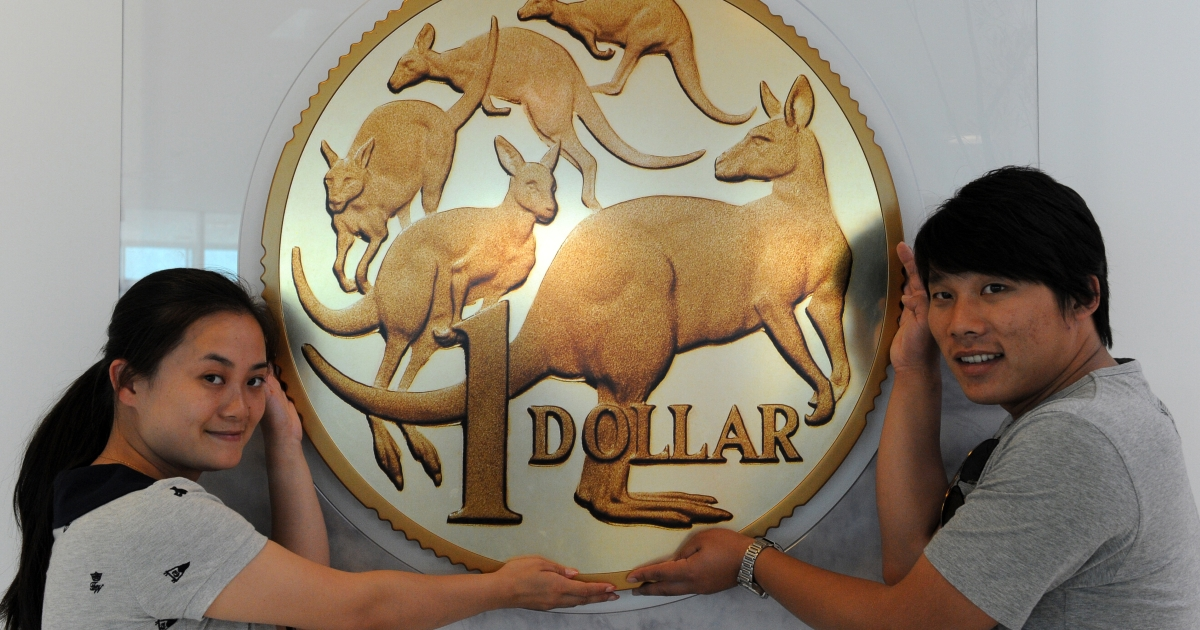 Chinese tourists Ren Yajing (L) and Wu Chong (R) support a giant Australian dollar display at the Royal Australian Mint in Canberra on October 21, 2011.</p>