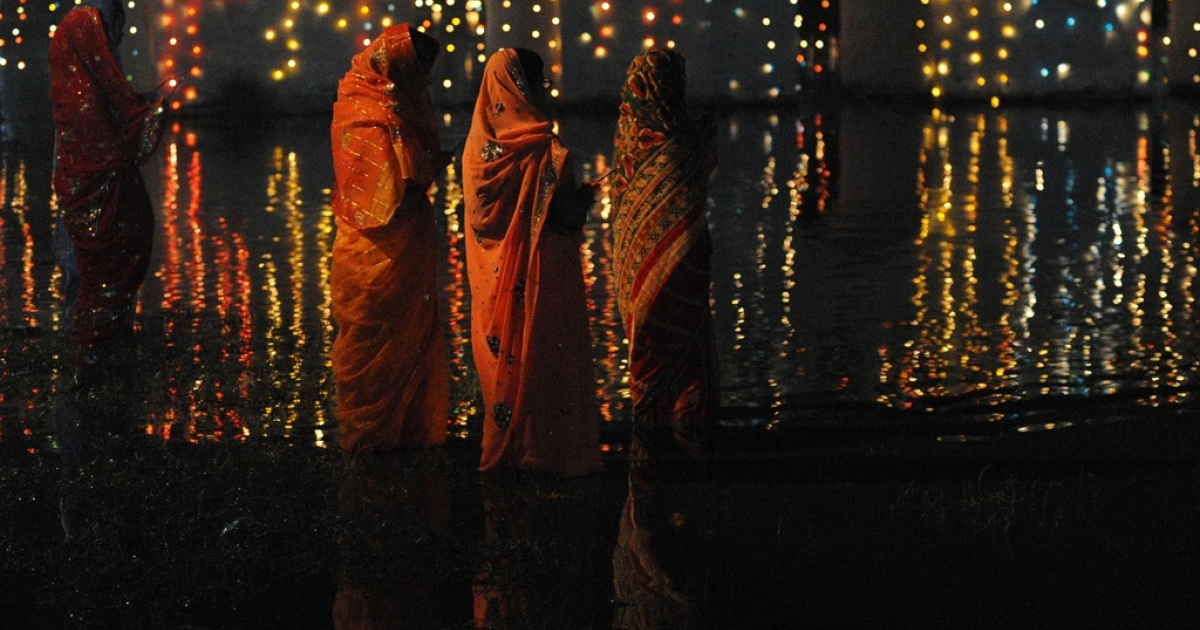 Nepalese Hindu devotees worship the rising sun as they stands in the Rani Pokhari during the Chhath festival, which honours the Sun God, in Kathmandu on November 2, 2011.</p>