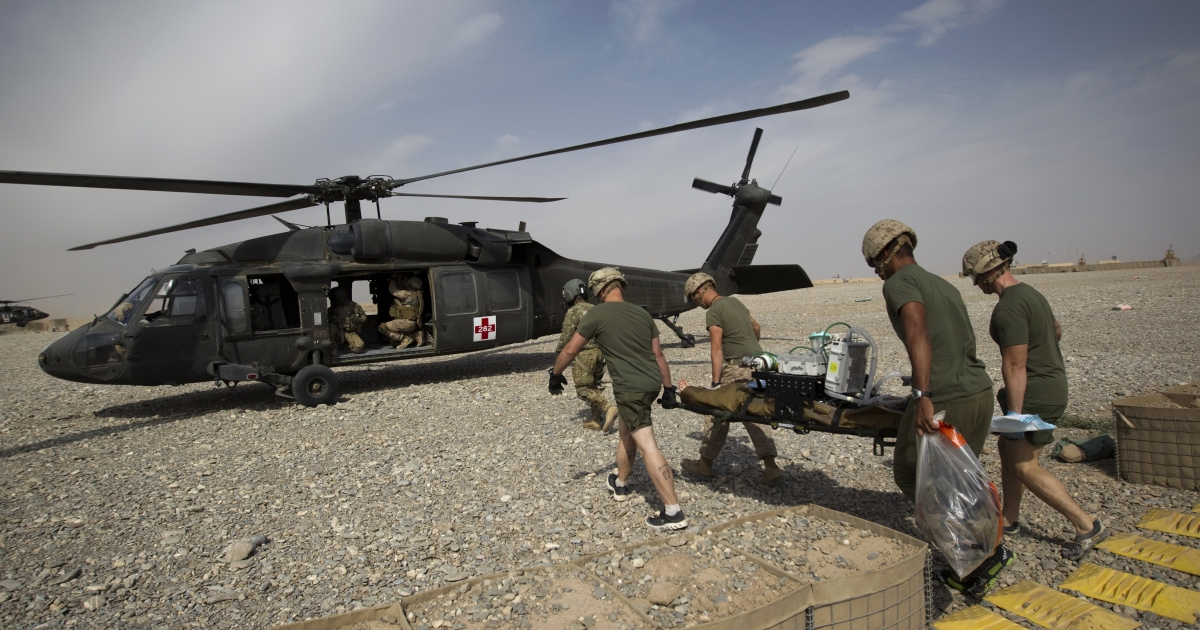 US Navy medical officers carry a wounded US Marine who was hit by an Improvised Explosive Device (IED) after amputating his leg to a medevac helicopter of US Army's Task Force Lift 'Dust Off', Charlie Company 1-171 Aviation Regiment in Helmand province on November 2, 2011.</p>