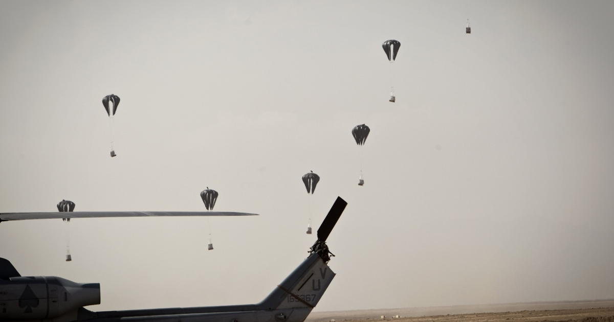 Supplies are airdropped by parachute from a helicopter for US Marines in the field as a UH-1 Yankee Huey combat helicopter is seen in the foreground at Forward Operating Base Edinburgh in Helmand province on November 9, 2011.</p>