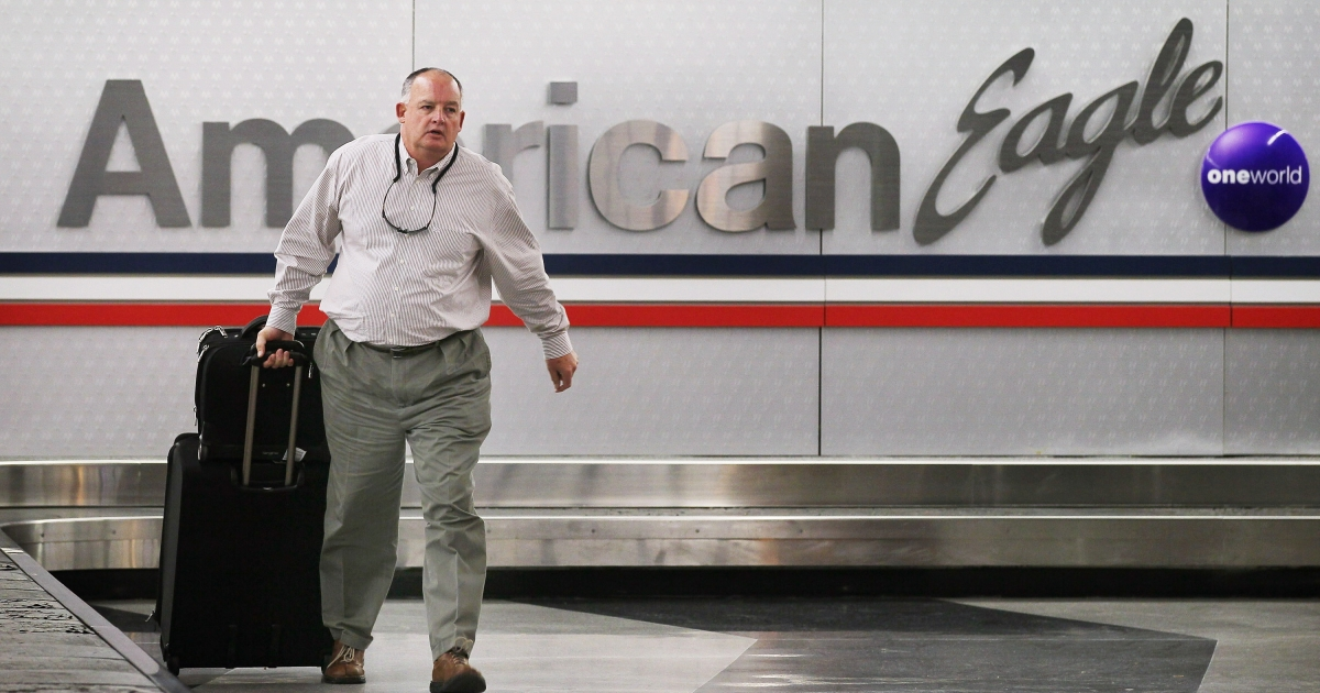 A passenger retrieves his luggage from a baggage conveyor that services American Eagle Airlines at O'Hare Airport on November 14, 2011 in Chicago, Illinois.</p>