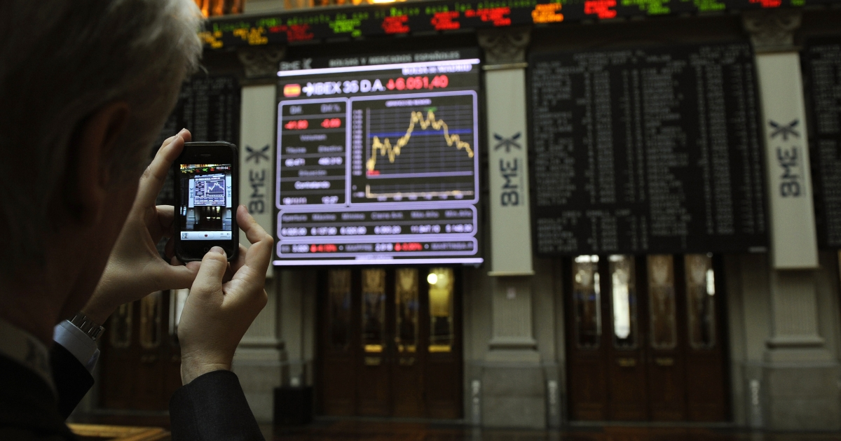 A man takes a picture with his mobile phone of a screen at Madrid's Stock Exchange. Bond yields have spiked due to worried investors.</p>