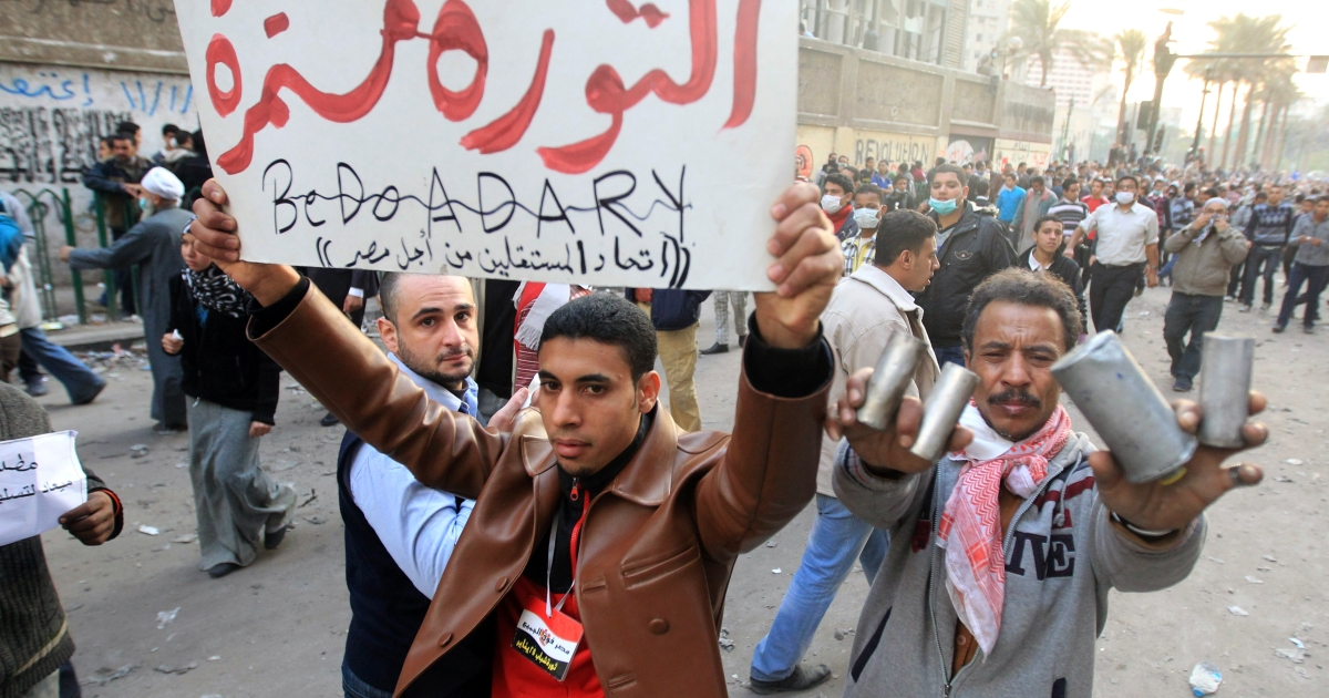 An Egyptian man holds up a banners that reads in Arabic,