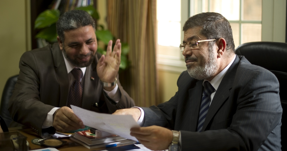 President of the Muslim Brotherhood-supported Freedom and Justice Party, Mohammed Morsi (R,) receives a piece of paper from an aide at the party headquarters in Cairo on November 28, 2011, as Egyptians cast their ballots in the first round of parliamentary elections.</p>