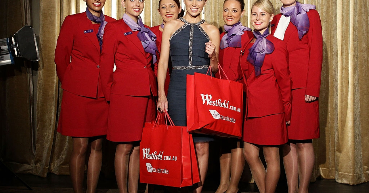 Dannii Minogue poses with Virgin flight crew during the launch of a partnership between Virgin Australia's frequent flyer program and Westfield on line at Westfield Sydney on November 29, 2011 in Sydney, Australia.</p>