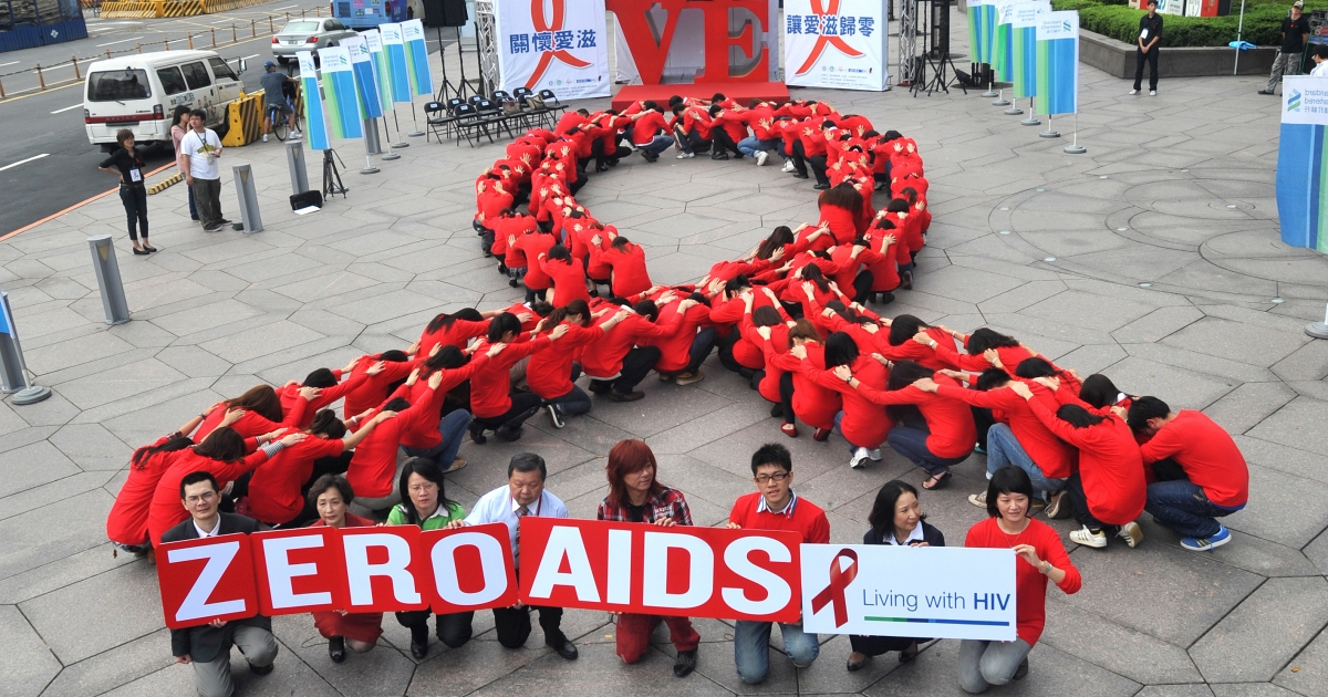 Dozens of volunteers join a human chain in the form of a red ribbon, a symbol of 'love and care' for HIV and AIDS carriers worldwide, at a gathering in downtown Taipei.</p>