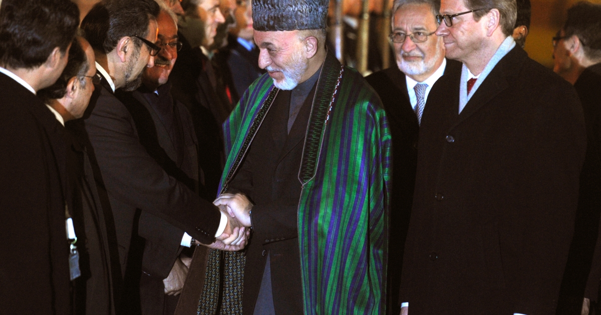 Afghan President Hamid Karzai (C) shakes hands with an unidentified man as he is welcomed by German Foreign Minister Guido Westerwelle (R) upon his arrival on December 2, 2011 at the Koeln/Bonn military airport, in Cologne, western Germany, ahead of a major international conference on Afghanistan.</p>