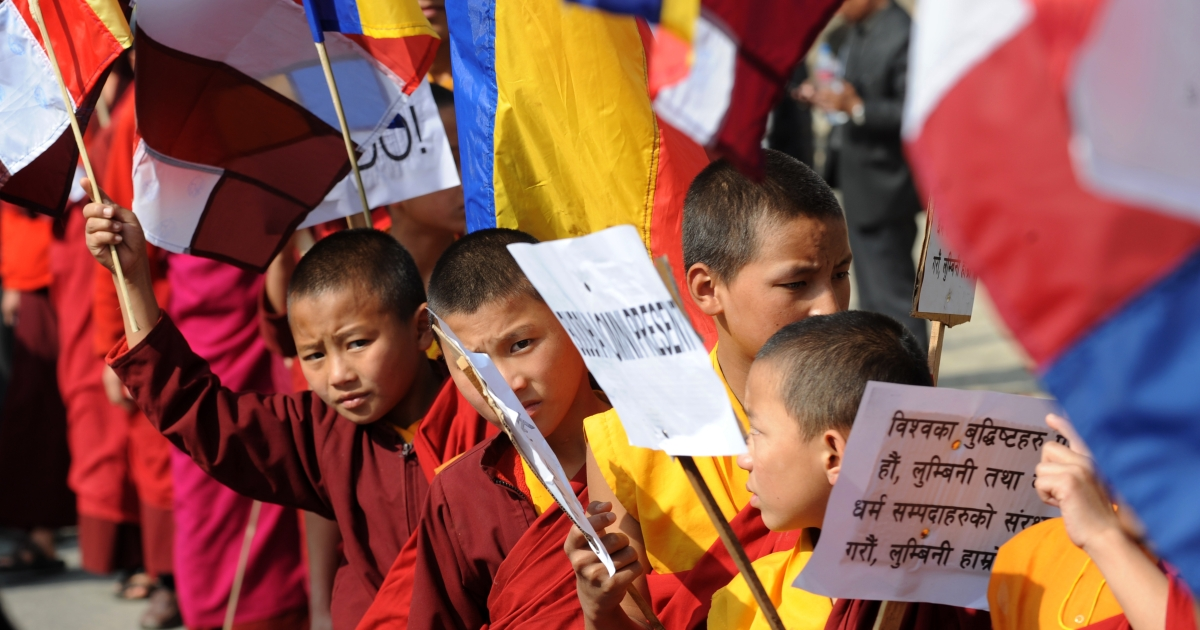 Nepalese Buddhist monks hold Buddhist flags and placards during a peace rally in Kathmandu on December 7, 2011.The organizers claimed that the Nepalese Buddhists have been unjustly bearing the discrepancies of Nepal's One China policy, which recognizes Tibet as its integral part.</p>