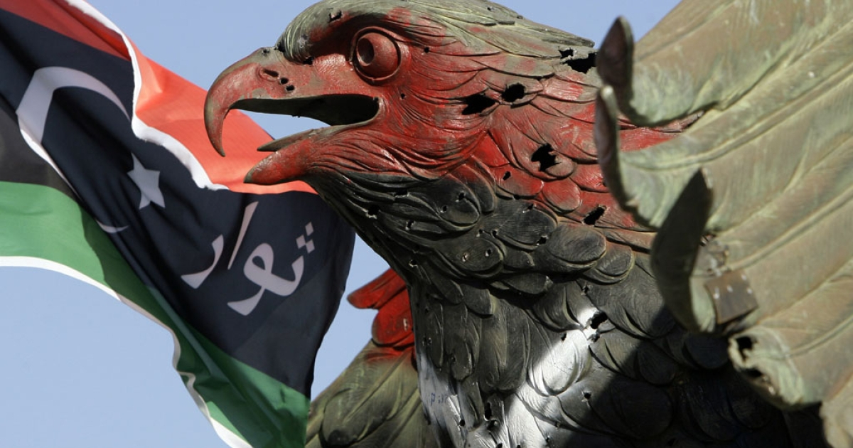 The new Libyan flag flutters near the bronze falcon that once decorated the Bab al-Aziziya compound of slain Libyan leader Muammar Gaddafi.</p>