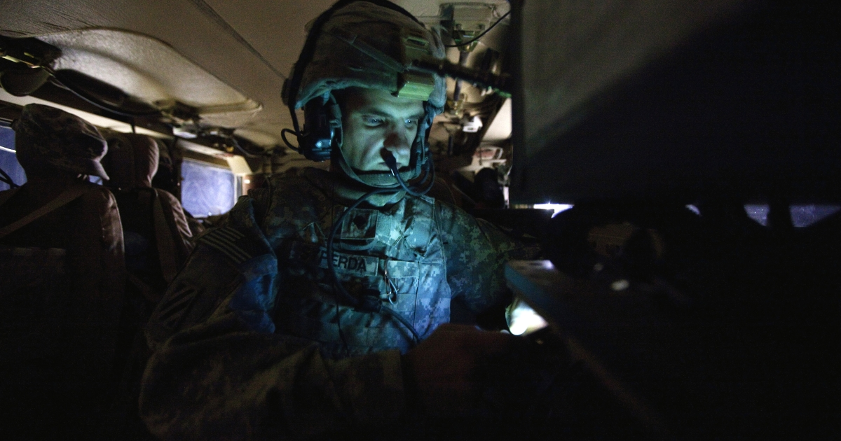 US Specialist Matthew Syperda of the 3rd Brigade Combat Team, 1st Cavalry Division looks at his cell phone inside his unit's Mine Resistant Ambush Protected (MRAP) vehicle during the US military's last combat patrol in Iraq on Highway 1, north of Camp Adder, near Nasiriyah on December 16, 2011.</p>