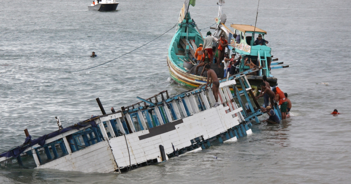 Rescuers check the wreckage of a people smuggler's boat seen half-submerged after being towed. Indonesian police arrested eight people December 22, 2011, in connection with the overloaded boat carrying 250 asylum seekers that capsized en route to Australia.</p>