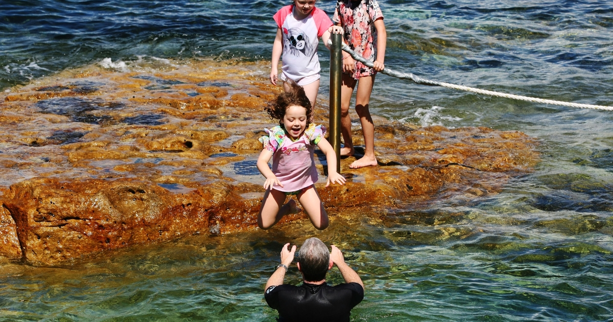 A young girl makes a perilous leap into her father's arms in the rockpools at Bondi Beach on Dec. 25, 2011 in Sydney, Australia.</p>