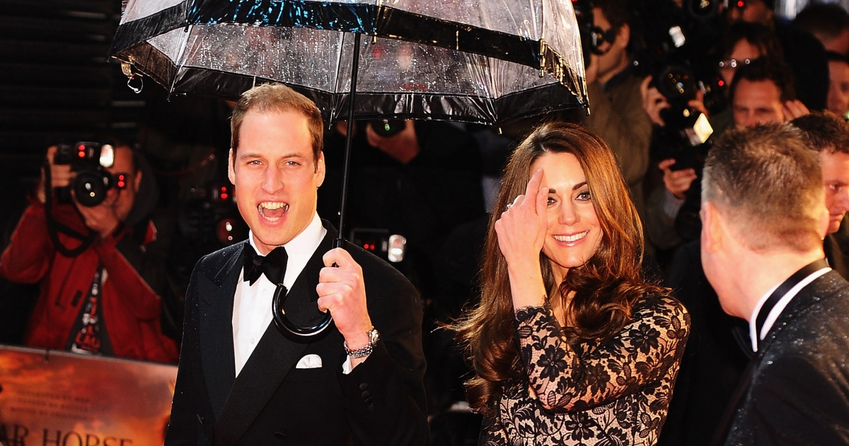 Britain's Prince William (L), Duke of Cambridge, and Catherine, Duchess of Cambridge (R), walk down the red carpet with an umbrella as they attend the UK premiere of US director Steven Spielberg's