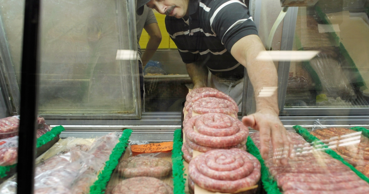 Robert Laurenzo places sausages in the display of the meat department at Laurenzo's Italian Center on January 9, 2012 in North Miami Beach, Florida.</p>