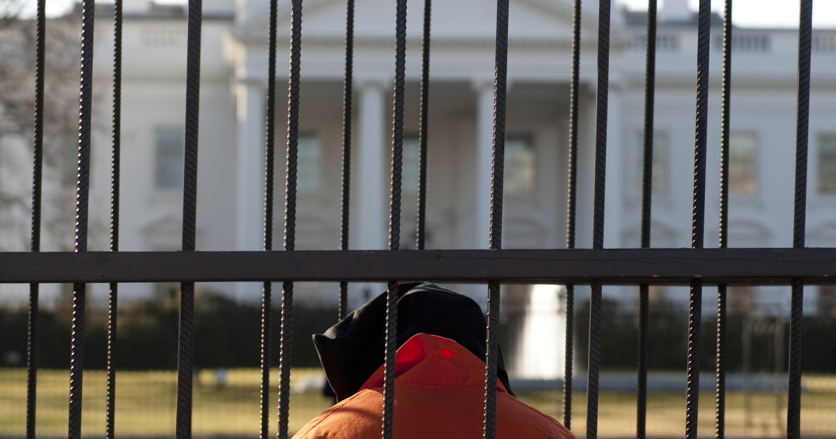 Beth Brockman of the organization Witness Against Torture wears an orange prison jump suit and a hood over her head as she sits in a cage during a demonstration in Lafayette Park outside the White House in Washington, DC, on January 10, 2012, urging the government to close down the detention facility at Guantanamo Bay.</p>