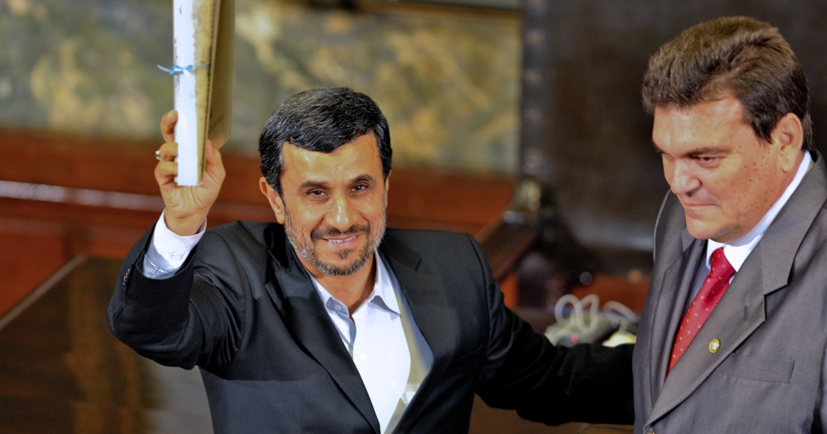 Iranian President Mahmoud Ahmadinejad (L) receives the Doctor Honoris Causa degree from the rector of Havana's University Gustavo Cobreiro, during a ceremony at the university in Havana, on January 11, 2012.</p>