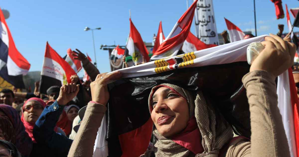 An Egyptian women covers her head in a national flag as she demonstrates in Cairo's Tahrir Square on January 27, 2012, ahead of a mass rally to demand democratic change, a year after the country's revolt that overthrew the regime.</p>
