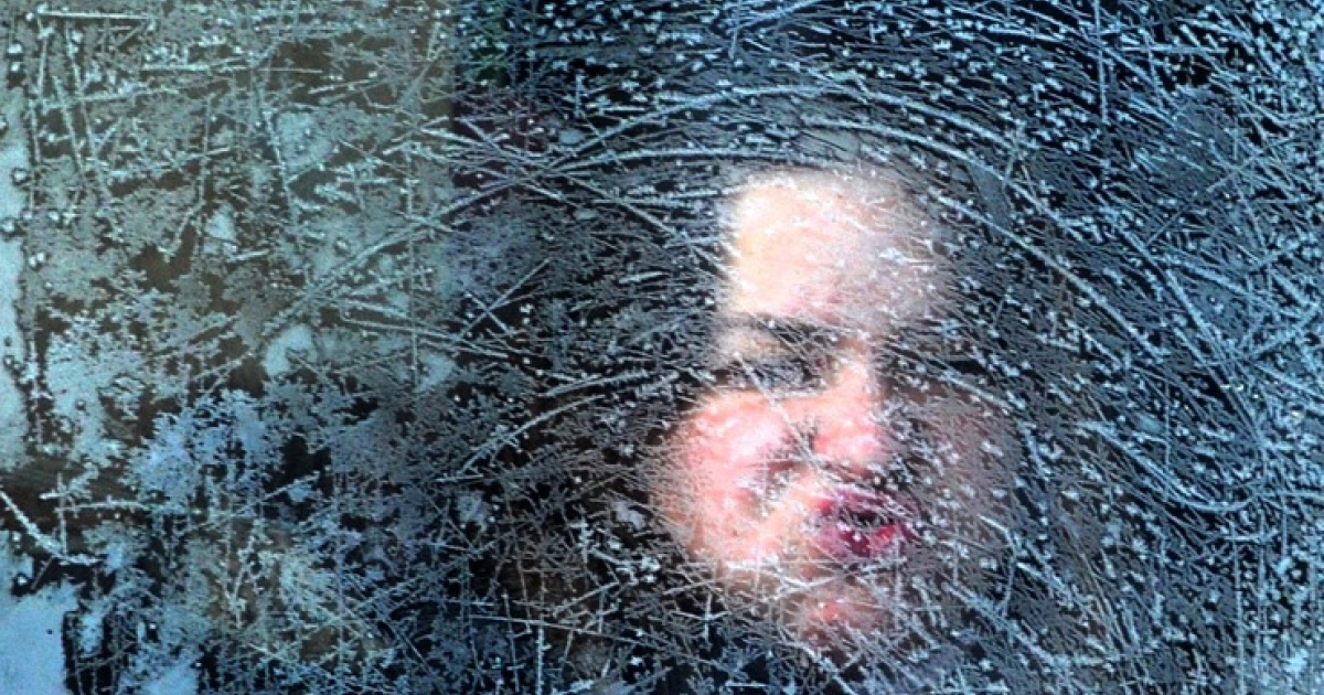 A woman looks through an icy window on a tram in Sofia on January 31, 2012. Record low temperatures were registered around Bulgaria on Tuesday, threatening shipping on the Danube and closing hundreds of schools.</p>
