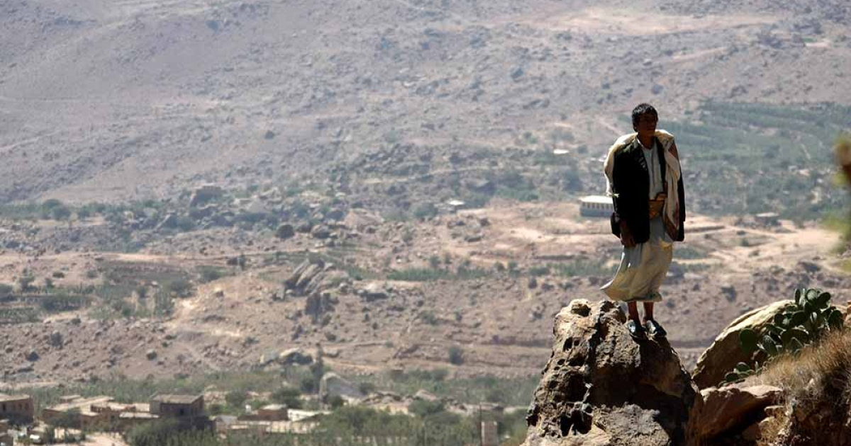 A Yemeni man stands on a rock on February 1, 2012 overlooking a village in Wadi Ahjar, some 50 kms northwest of Sanaa.</p>