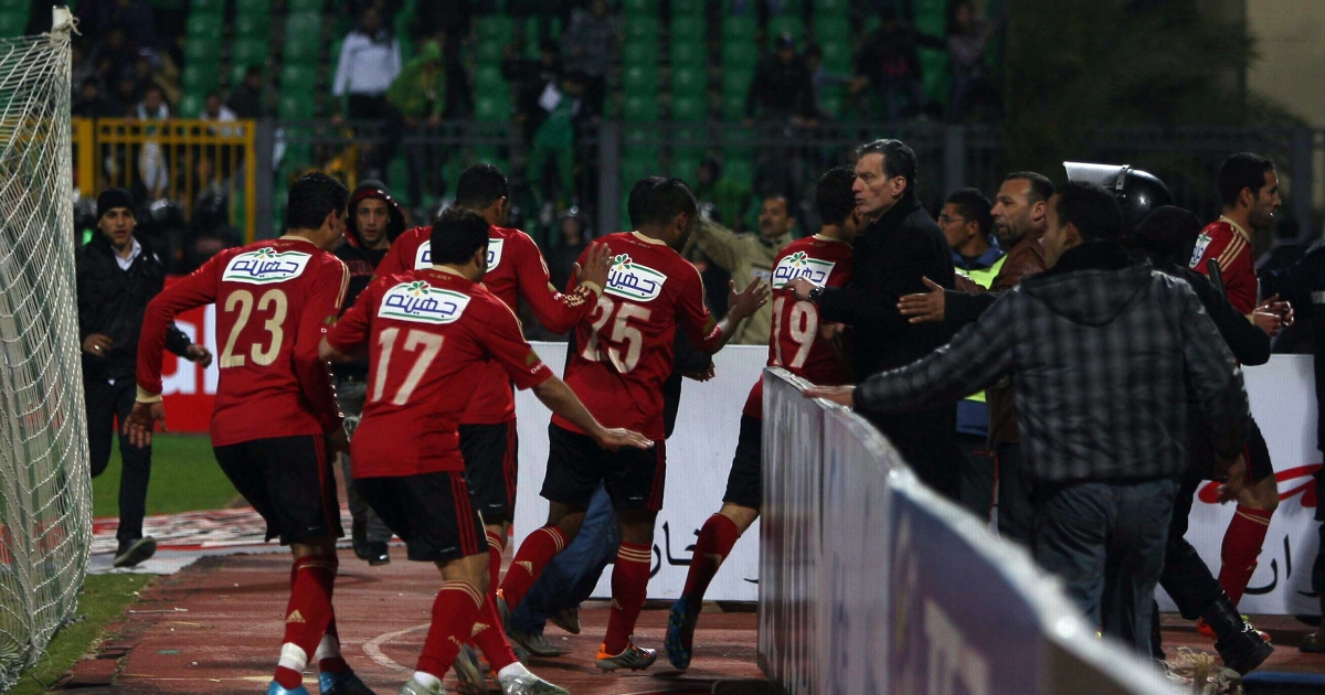 Egyptian Al-Ahly players escape from the field as fans of Al-Masry team rush to the pit during clashes that erupted after a football match between the two teams in Port Said.</p>
