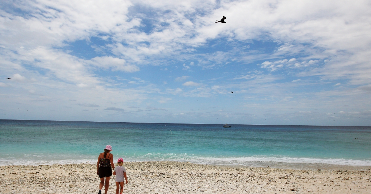 A woman and her daughter walk along the beach at Lady Elliot Island, a resort on the Great Barrier Reef.</p>