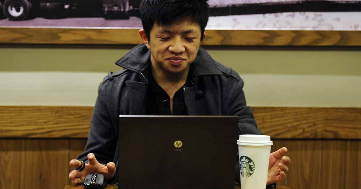 A man uses his computer in a coffee shop in Shanghai on February 2, 2012. PETER PARKS/AFP/Getty Images</p>