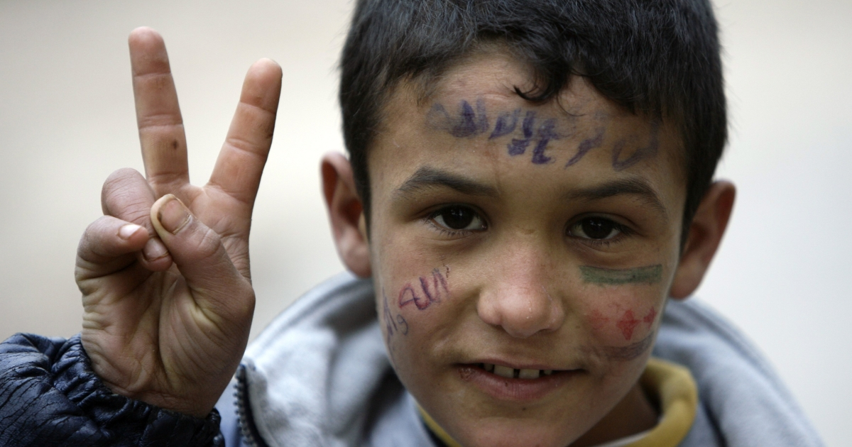 A young Syrian refugee who fled with his family the violence in Homs, flashes the V for 'victory sign as he takes shelter in the area of Wadi Khaled on the borders with Syria, north of Lebanon, on February 10, 2012.</p>