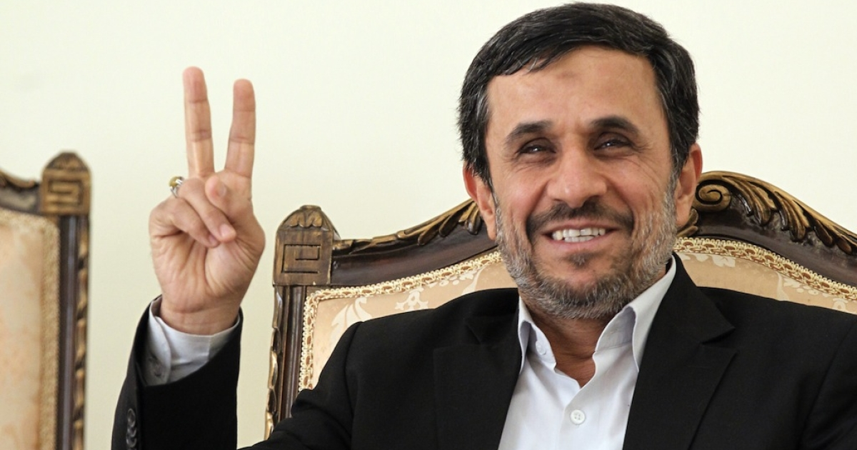 Iranian President Mahmoud Ahmadinejad flashes the V-sign for victory as he waits for the arrival of Ismail Haniya, Palestinian Hamas premier in the Gaza Strip, for a meeting in Tehran on February 12, 2012.</p>