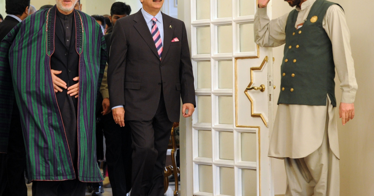 Hamid Karzai, Afghanistan's President, arrives with Pakistan's Prime Minister Yousuf Raza Gilani (2R) at the Prime Minister's House in Islamabad on February 16, 2012.</p>