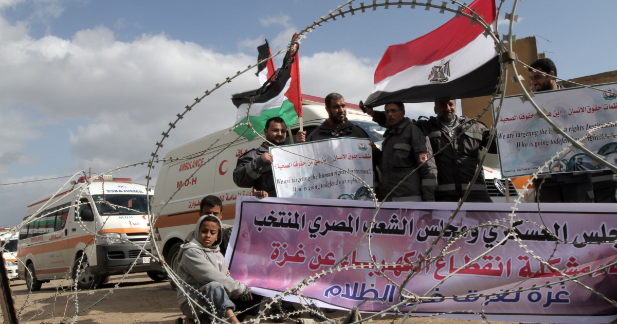 Palestinians attend a rally in front of the Rafah border crossing with Egypt on February 18, 2012 during a sit-in by dozens of emergency crews and ambulance workers demanding Egypt provide the Gaza Strip with electricity and diesel.</p>