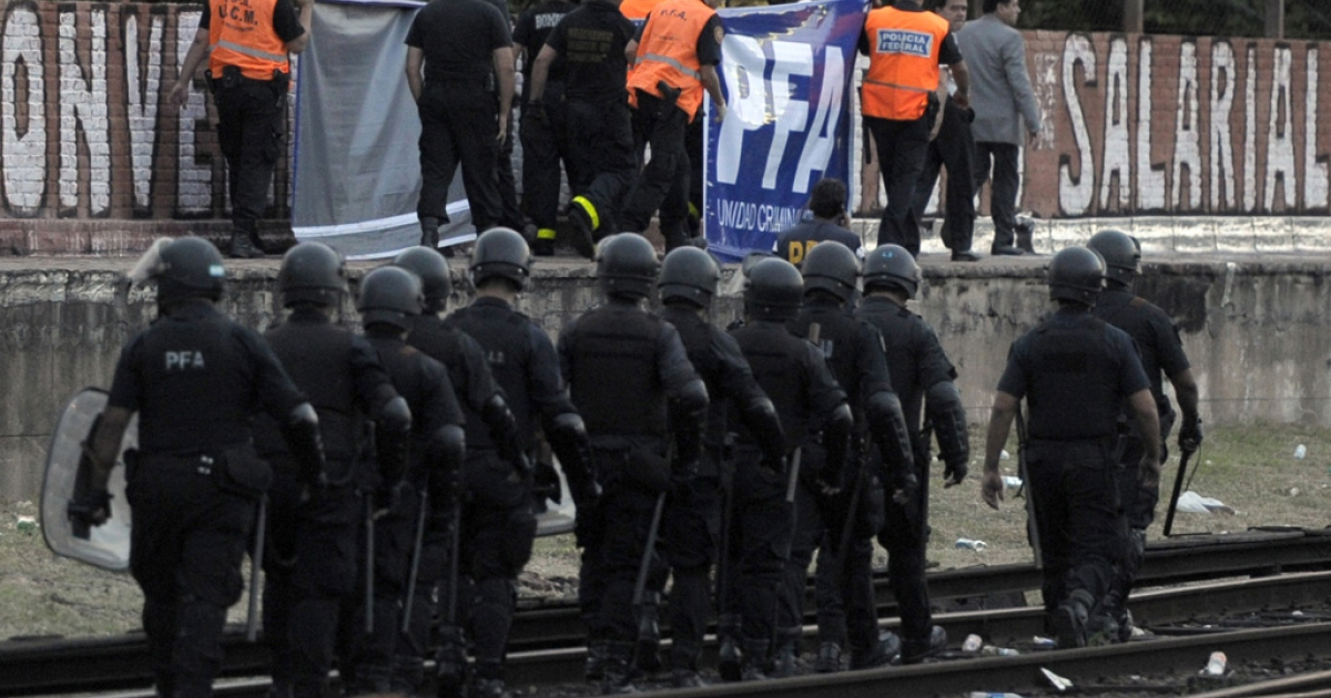 Rescuers and riot police remove the body of Lucas Menghini Rey from the Once train station today in Buenos Aires.</p>