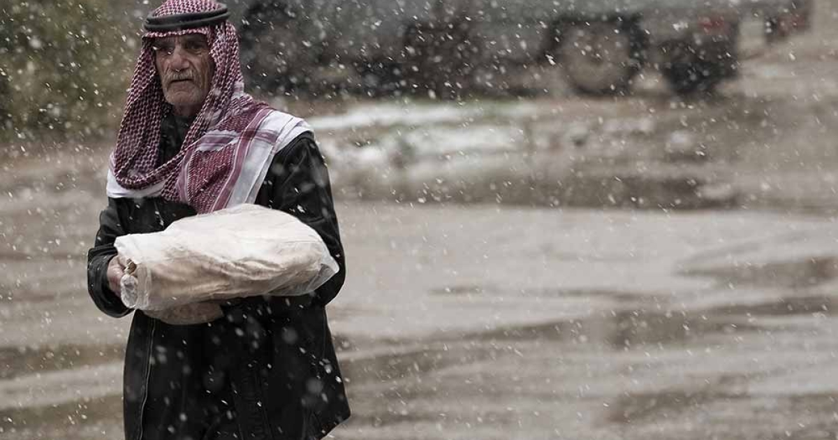 A Syrian man carries bread from a nearby bakery as he walks under the snow in Qusayr, 15 kms (nine miles) from Homs, on March 1, 2012. Gianluici Guercia/AFP.</p>