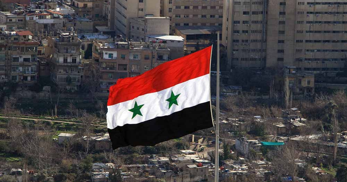 A Syrian flag flies over Damascus on March 1, 2012 .</p>