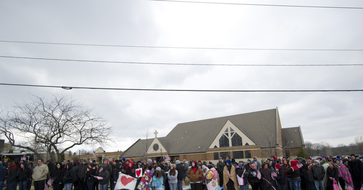 A crowd stands along the road in front of Church of St. Mary before Danny Parmertor's funeral today in Chardon, Ohio. Parmertor died Monday during a school shooting that killed 3 and injured 2 more. TJ Lane faces murder charges in the incident.</p>