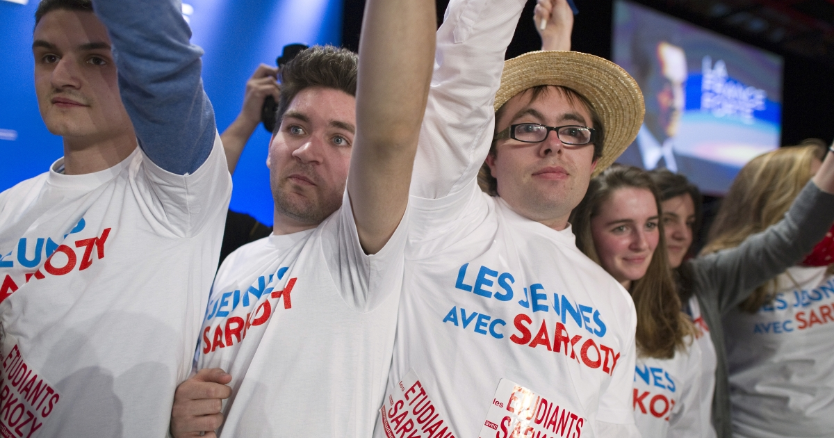 Supporters wearing tee-shirts reads 'Young people with Sarkozy' waves flags as they listen France's ruling party UMP candidate for the 2012 French presidential election Nicolas Sarkozy during a campaign meeting, on March 3, 2012 in the southwestern city of Bordeaux.</p>