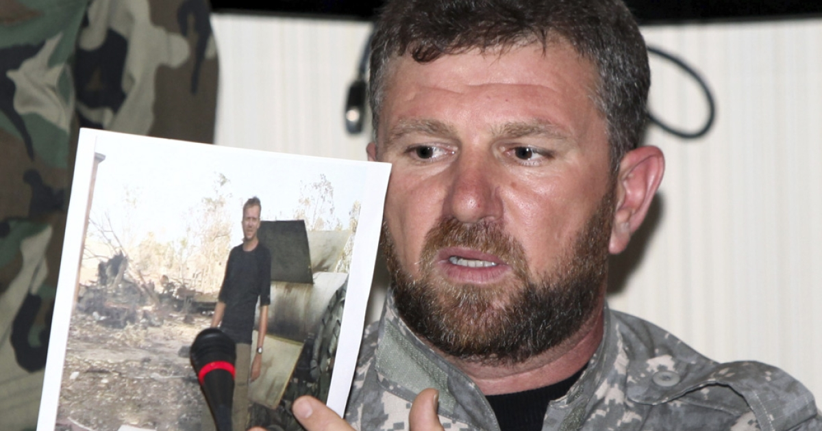 The commander of the Libyan Swehli militia, Faraj Swehli, holds up a photograph of British journalist Gareth Montgomery-Johnson during a press conference in Tripoli.</p>